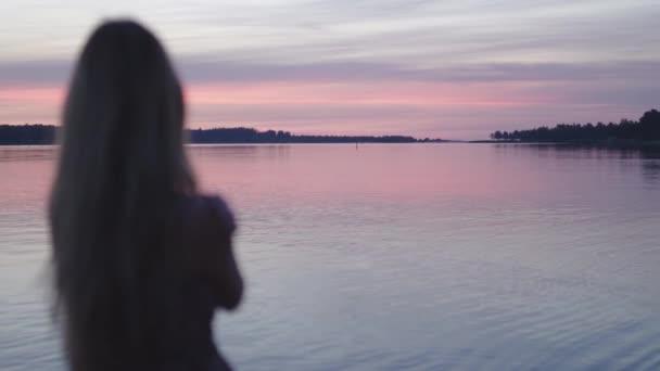 junge Frau im kurzen Sommerkleid, die in der Nähe des Flusses steht und das Leben und die Natur genießt, im Hintergrund bei Sonnenuntergang