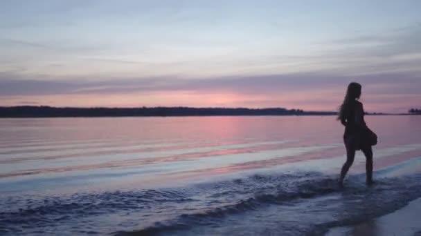 junge Frau im kurzen Sommerkleid spaziert am Strand entlang und genießt das Leben und die Natur weit entfernt im Hintergrund bei Sonnenuntergang