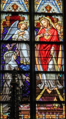 's Hertogenbosch, The Netherlands - July 23, 2011: Stained Glass Window depicting Saint Margaretha Maria in adoration to the Sacred Heart of Christ in Den Bosch Cathedral, North Brabant.