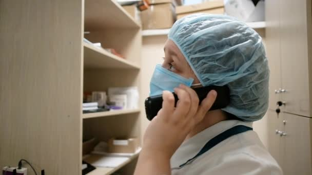 pharmacist woman 40-50 years old in a pharmacy talking on the phone. Specialist surgeon in the clinic. Pharmacy selling drugs.