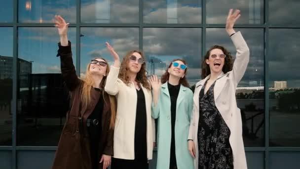 skupina pěti krásných dívek mává. mladí lidé. Koncept cestovního ruchu. Šťastné léto. Zábava. Na pozadí toho města. 20-25 let