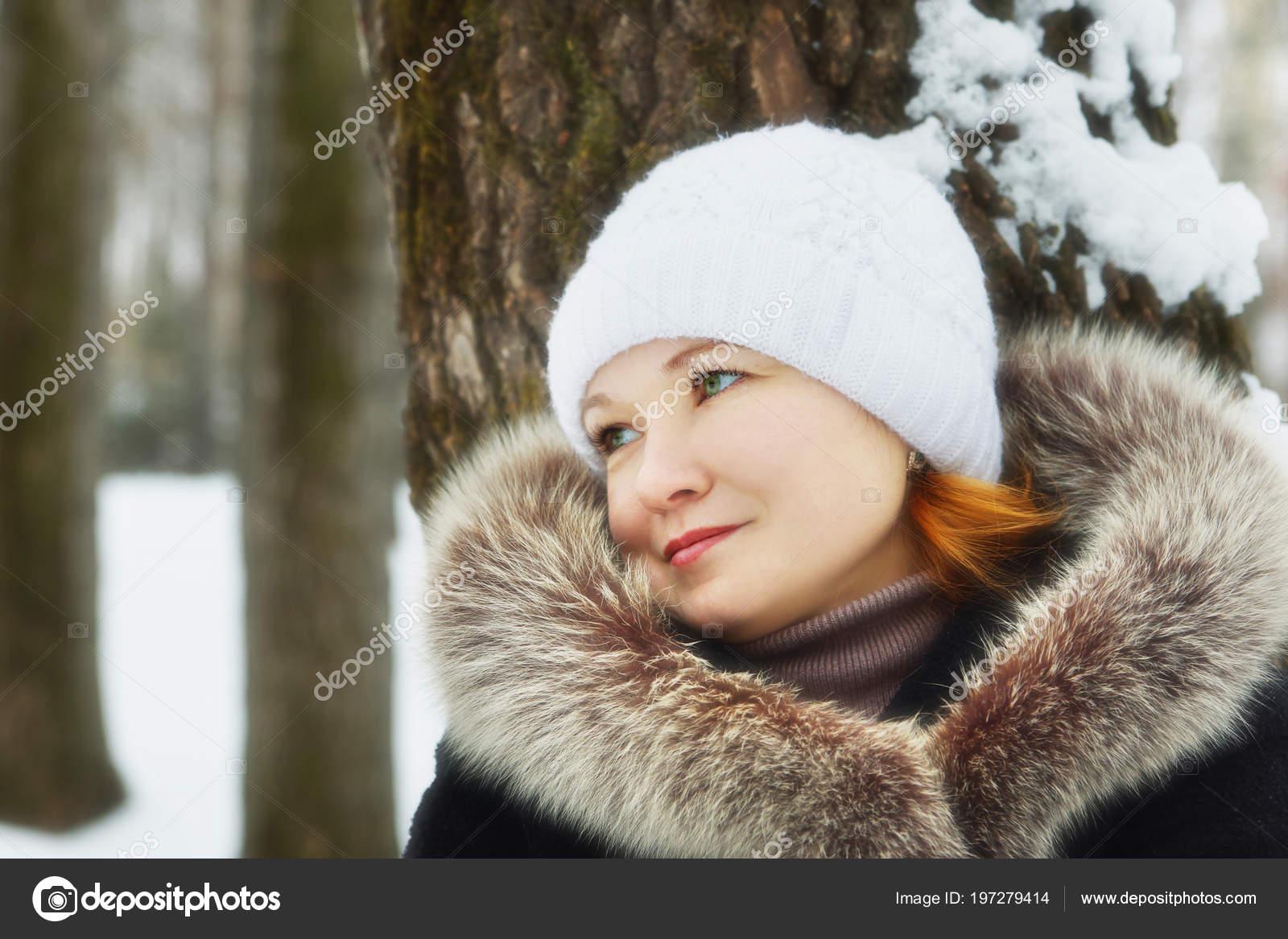 0d6cc526f6b4 Νέοι όμορφη γυναίκα που φοράει ένα παλτό με γούνινο γιακά αφράτο και λευκό  πλεκτό καπέλο έγειρε το δέντρο σε ένα χειμερινό πάρκο σε εξωτερικούς χώρους  ...