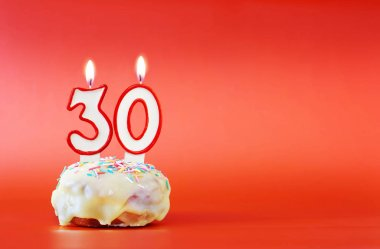 Thirty years birthday. Cupcake with white burning candle in the form of number 30