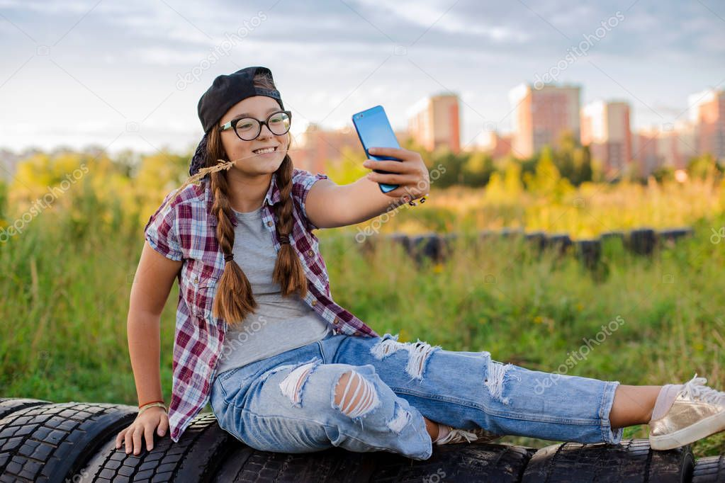 girl teenager in glasses sits the ground city background in the headphones of selfie smartphone