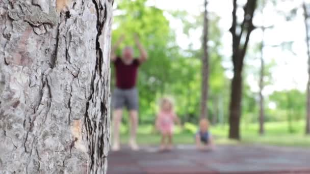 Grandfather playing and jumping with grandchildren outside in the park