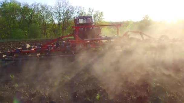 Farmář v traktoru půdě pluhy steadicam pohybu zemědělství zemí Rusko připravuje půdu s Záhonový kultivátor jako součást pre secí aktivity v životním stylu časně jarní sezóny zemědělských