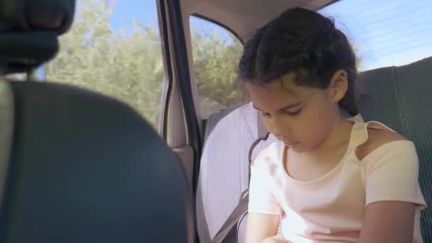 sad girl bored sitting in the car in the back seat travel. little girl bored in the car. concept long motion journey