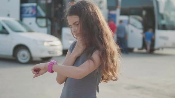 little girl looks at smart slow motion video internet clock social media. girl teenager at the bus station leaves tourism waiting for the bus. lifestyle concept of technology travel