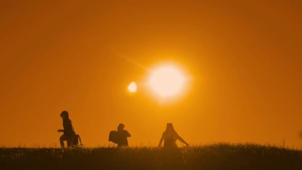 lidé pěší skupina štěstí hodit batohy svobodu spouštět a silueta psa slunečního záření turistů čtyř lidí, kteří jdou na vrcholu hory slunce siluetu. Zpomalený pohyb běžící video