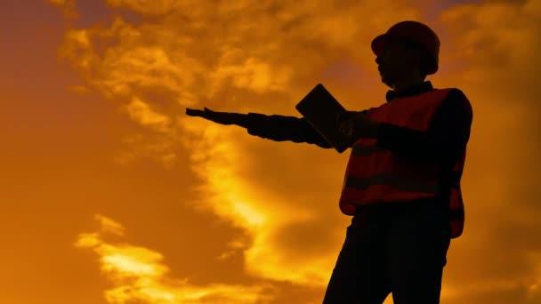 inženýr silueta drží žluté pracuje na tabletu helma pro bezpečnost pracovníků na pozadí. Tvůrce v pojetí helmy