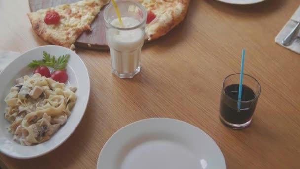 dospívající chlapci a dívky jí pizza café zpomalené video. děti jedí pizzu vynikající pizzu. Společnost přátel lidí na životní styl v kavárně. děti, které jedí pizzu koncept