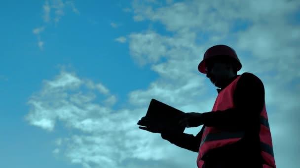 inženýr silueta drží žlutá helma funguje na tabletu pro bezpečnost pracovníků na pozadí. životní styl tvůrce koncepce helma