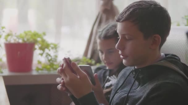 children are sitting in a cafe playing games in the smartphone slow motion video. boy and girl teens social media on smartphone. kids children and lifestyle smartphone concept
