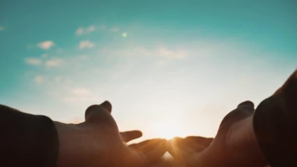 adam elini güneşe doğru çekiyor. doğa güneş ışığı siluet bir adamın elini. kavram özgürlük yaşam tarzı din güneş. adam ellerini güneşe genişletir