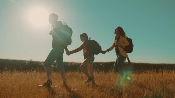 šťastná rodina komáři jít, zpomalené video chůze na přírody kluk holka a maminka v poli na pěší výlet do životního stylu. turisté s kytarou batohy, cestování. šťastná rodina venku cestování Turistika