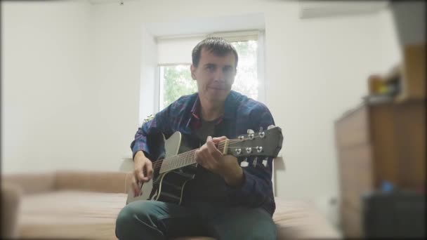 Handsome young musician playing the guitar and singing. Man Playing Acoustic Guitar Close Up slow motion video. in the room sits on the couch. man and guitar lifestyle concept