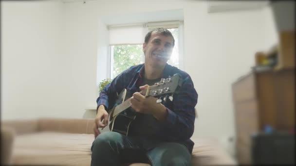Pohledný mladý hudebník hraje na kytaru a zpívá. Člověk hraje akustická kytara úzké až zpomalené video. v místnosti životní styl sedí na gauči. koncept muž a kytara