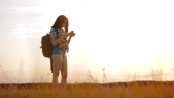 Hipster hiker silhouette girl wanderer search position navigation on mobile phone smartphone to find right way during adventure nature travel. woman hiker checks weather forecast via cell telephone