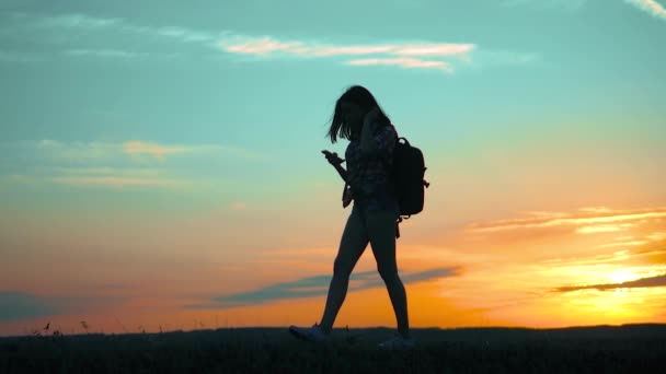 silhouette hiker girl traveler with smartphone navigation search ways. the girl nature search position navigation slow motion video silhouette girl travel lifestyle concept woman