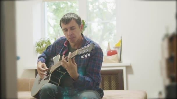 Mužské hudebník hraje akustická kytara. muž si hraje akustickou životní styl kytara zpomalené video. v místnosti sedí na gauči. koncept muž a kytara