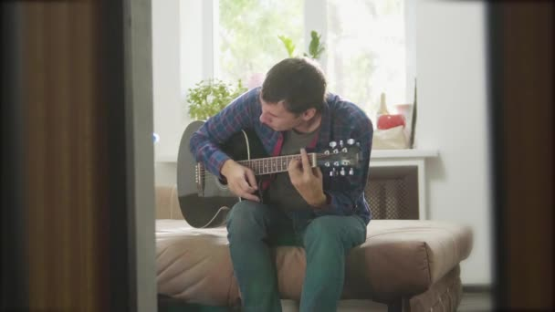 muž kytarista hraje hudbu dřevěné akustická kytara. Člověk hraje akustická kytara úzké až zpomalené video. v místnosti sedí na životní styl pohovky. koncept muž a kytara