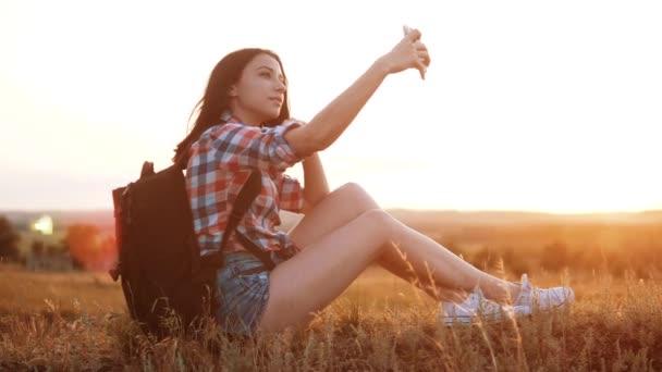 Bokovky tramp silueta dívka cestovatel odpočinku odpočinku zpomalené video s batohem dělá take selfie autoportrét cestovní blog. životní styl dívka selfie cestování koncept