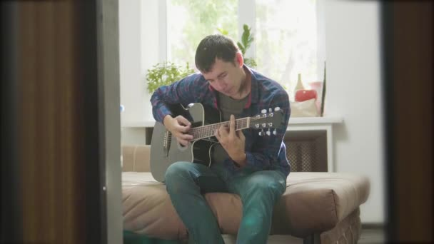 Acoustic Guitar Playing. Men Playing Acoustic Guitar Close Up slow motion video. in the room sits on the couch. man and guitar concept lifestyle