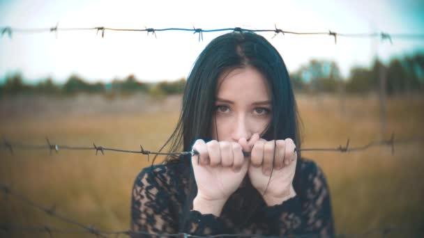 dívka Bruneta uprchlíků za ostnatým drátem tábor zpomalené video. životní styl pojetí svobody je naštvaný, co žena ruce a ostnatým drátem. dívka uprchlíka, vězení, uprchlíci zajetí koncept