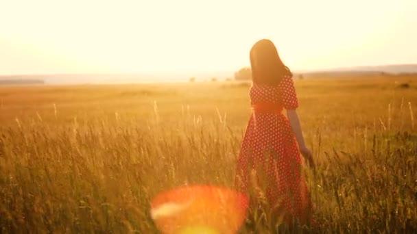 Krásná mladá dívka na poli s květy, užívat si přírody venku zpomalené video. dívka v poli při západu slunce v červených šatech životní styl ruka close-up na siluetu sluneční světlo trávy