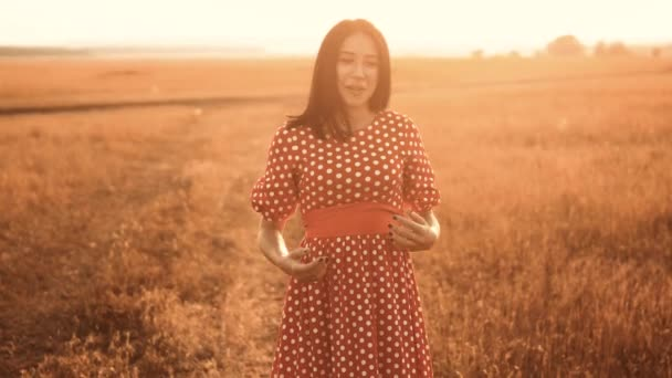 Young girl in red dress shy smiles grass nature slow motion video. girl in the field shy smiles sunset in a red dress hand close-up on the grass sunlight silhouette. woman shy smiles in the field