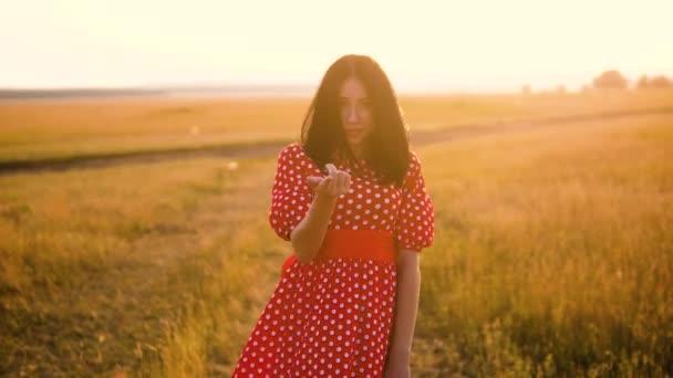 roztomilý sexy brunetka kýval na fotoaparátu, vyzývající k lásce flirtování trávy příroda zpomalené video silueta při západu slunce. dívka v červených šatech na přírodu se smát emoce úsměv životní styl. přírodní žena