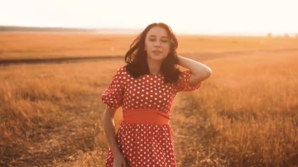 roztomilý sexy brunetka kýval na fotoaparátu, vyzývající k lásce flirtování trávy příroda zpomalené video silueta při západu slunce. dívka v červených šatech na emoce úsměv smích přírody. životní styl žena příroda