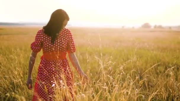 Beautiful young girl walking on field with wildflowers, enjoying nature outdoors Slow motion video. girl in the field at sunset in a red dress hand close-up on the grass sunlight silhouette lifestyle