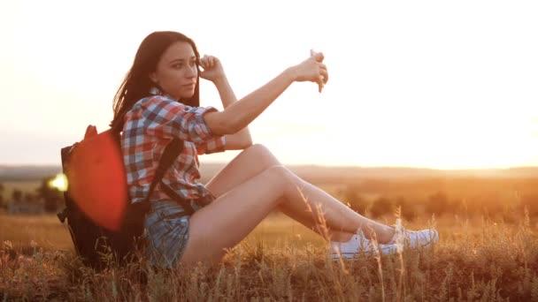 Bokovky tramp silueta dívka cestovatel odpočinku odpočinku zpomalené video s batohem dělá take selfie autoportrét cestovní blog. dívka selfie životní styl cestování koncept