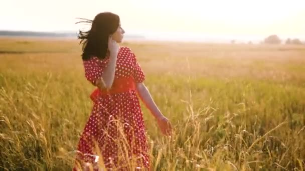 Beautiful young girl walking on field with wildflowers, enjoying nature outdoors Slow motion video. girl in the field at sunset in a red dress hand close-up on the grass sunlight silhouette. woman