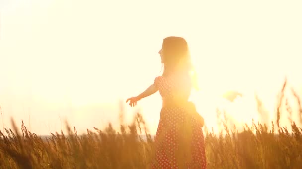 slow motion video. beautiful girl whirls in the field hands in the hand silhouette at sunset sunlight. woman concept lifestyle freedom joy happiness travel