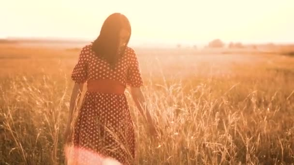 Beautiful young girl walking on field with wildflowers, enjoying nature outdoors Slow motion video. girl in the field at sunset in a red dress hand close-up on the grass sunlight lifestyle silhouette