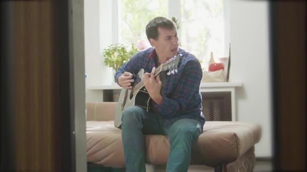 muž si hraje hudbu dřevěné akustická kytara. Člověk hraje akustická kytara úzké až zpomalené video. v životním stylu místnosti sedí na gauči. koncept muž a kytara