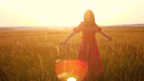 slow motion video. beautiful girl whirls in the field hands in the hand silhouette lifestyle at sunset sunlight. woman concept freedom joy happiness travel