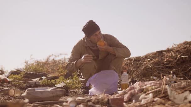 portrét špinavé hladový bezdomovec v díře jíst oranžová pro jídlo v balíčku s pohybovými hledají jídlo slow motion video. špinavé bezdomovce muž bez střechy osoba hledá jídlo v