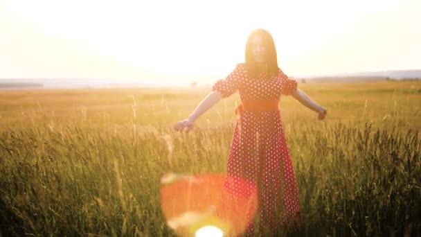 slow motion video. beautiful girl whirls in the field hands in the hand silhouette at lifestyle sunset sunlight. woman concept freedom joy happiness travel