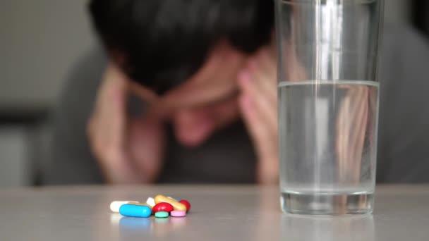 Mann, der Tabletten zu Hause nimmt, ist krank krank Zeitlupe Video. Gesundheitswesen Lebensstil und medizinische Konzept Krankheit. Männchen nimmt Tablette und trinkt drinnen ein Glas Wasser