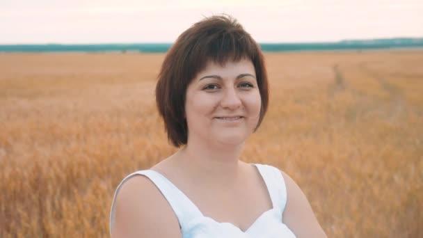 portréja egy kövér zsíros nő mosolyogva. Plusz-size divat modell lassú mozgás Video fehér ruha, a mező a búza. kövér nő a természet, fű mező virág nyáron. mezőgazdasági túlsúlyos nő