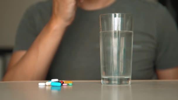 Mann, der Tabletten zu Hause nimmt, ist krank krank Zeitlupe Video. Gesundheitswesen und medizinisches Konzept Krankheit. Männchen nimmt Lifestyle-Pille und trinkt ein Glas Wasser im Haus