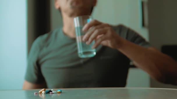 Mann, der Tabletten zu Hause einnimmt, ist krank in Zeitlupe Video. Gesundheitswesen und medizinisches Konzept Krankheit. Männchen nimmt Tablette und trinkt drinnen ein Glas Wasser