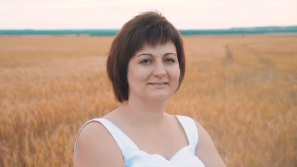 Porträt einer fett fette Frau lächelnd. Plus Size Mode-Modell in Slow-Motion Video weiß Kleid auf Feld Weizen. Fette Frau auf Natur im Bereich Rasen Blumen Sommer. Landwirtschaft-Übergewicht-weiblich