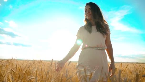 Mädchen läuft in Zeitlupe am Weizenfeld entlang. schöne Mädchen in weißem Kleid läuft die Natur Freiheit Glück Hände zur Seite auf dem Feld bei Sonnenuntergang Licht und den blauen Lifestyle-Himmel