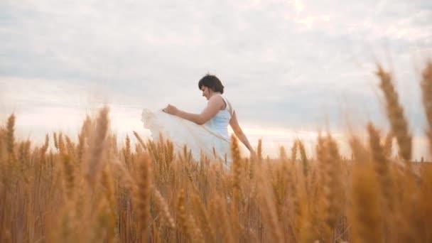 Plus Size Mode-Modell in Slow-Motion-video Fuß weißes Kleid auf Feld Weizen. Fette Frau auf die Natur in den Bereich Rasen Blumen Sommer Lifestyle. Landwirtschaft Übergewicht Frauenkörper. volle Mädchen Länge