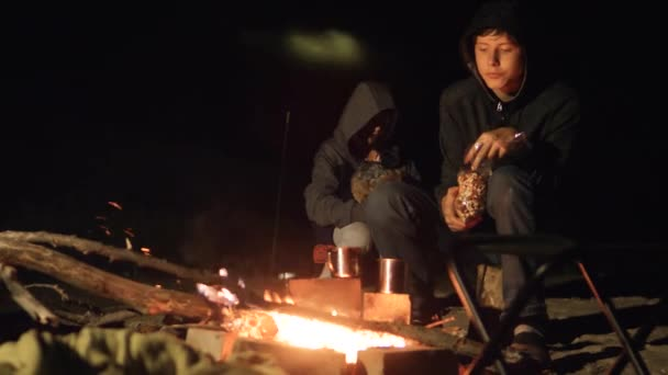 children smile kids drink tea teen sit by the fire at night campfire lifestyle. travel hiking adventure camping adventure camping. tourists are warming themselves by the fire. kids hikers concept
