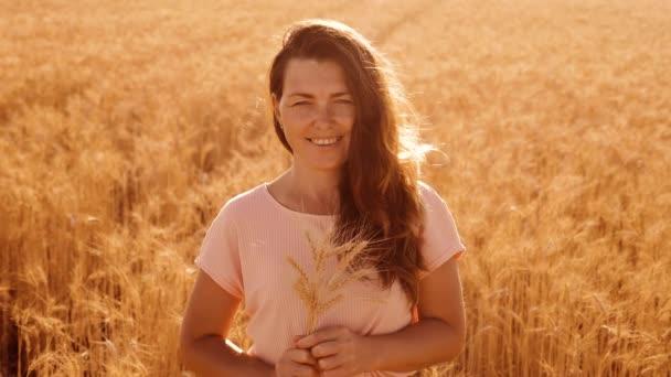 portrét krásná žena s úsměvem. Modelka dívka v zpomalené video bílých šatech na pole pšenice. sexy žena na přírodu v létě květy pole trávy. zemědělství. dívka délka portrét příroda